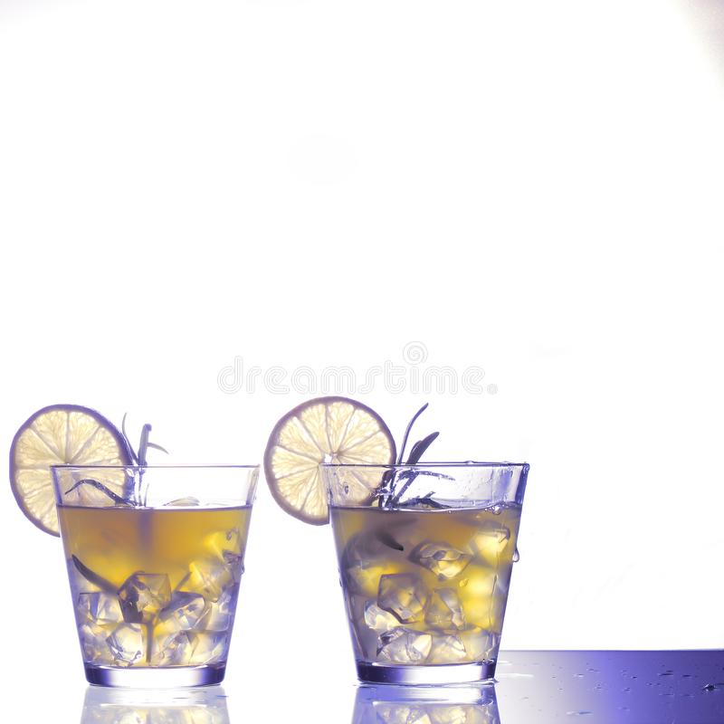 Dwa żółtego koktajlu z cytryny i trawy pozycją na szkle w studiu, fantazja barwili obraz stock