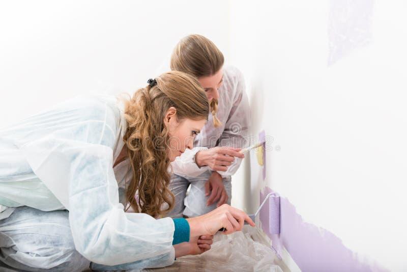 Dwa żeński pracownik daje purpurom barwi na ścianie fotografia stock
