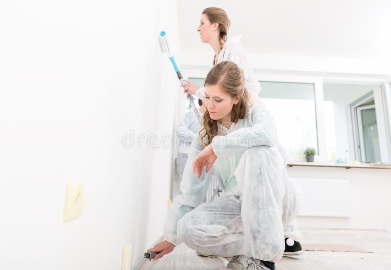 Dwa żeński pracownik maluje ścianę zdjęcia stock