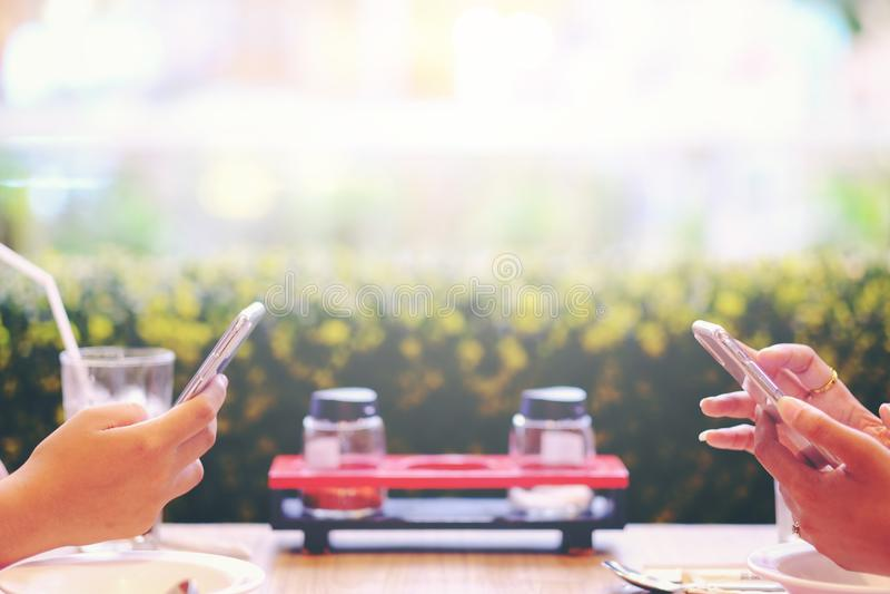 Dwa żeński używa telefon komórkowy na jedzenie stole obraz royalty free