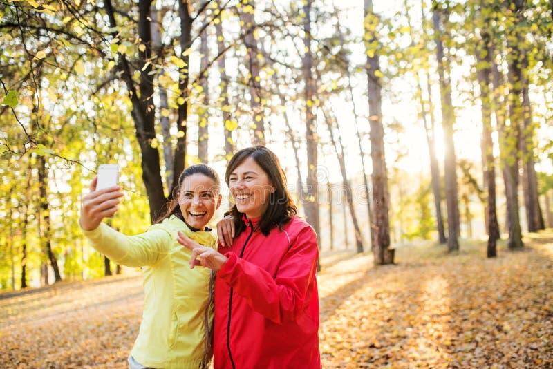 Dwa żeńskiego biegacza z smartphone bierze selfie outdoors w lesie w jesieni naturze fotografia stock