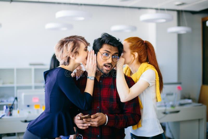 Dwa żeńskiego biurowego workes wispering znacząco wiadomość Indiański szef obraz stock
