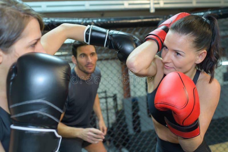 Dwa żeńskiego boksera walczy w sprawności fizycznej centrum zdjęcia stock
