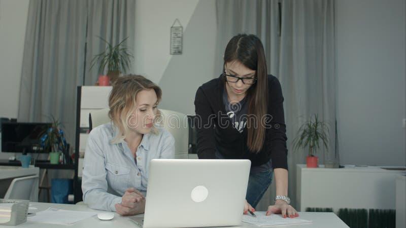 Dwa żeńskiego coworkers wymienia pomysły o raportowym patrzeje laptopie obrazy stock