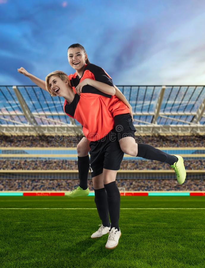 Dwa żeńskiego gracza piłki nożnej świętuje zwycięstwo na piłce nożnej segregującej obraz royalty free