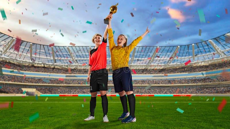 Dwa żeńskiego gracza piłki nożnej trzyma zwycięstwo filiżankę na zatłoczonym stadium fotografia royalty free