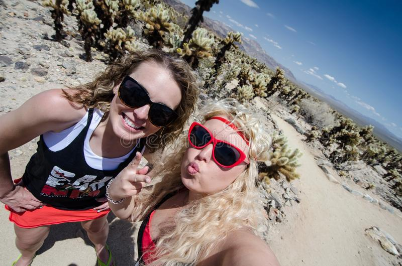 Dwa żeńskiego przyjaciela biorą selfie przy Cholla kaktusa ogródem w Joshua drzewa parku narodowym zdjęcie royalty free