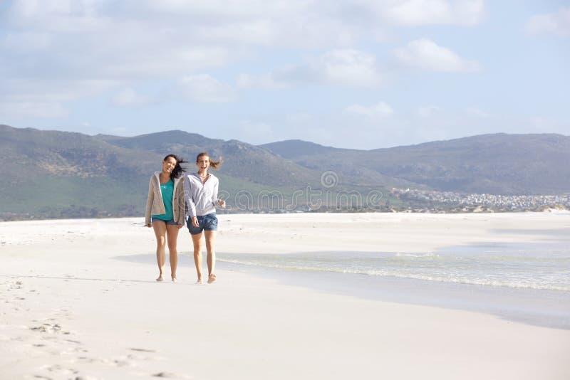 Dwa żeńskiego przyjaciela chodzi na pustej plaży wpólnie zdjęcie royalty free