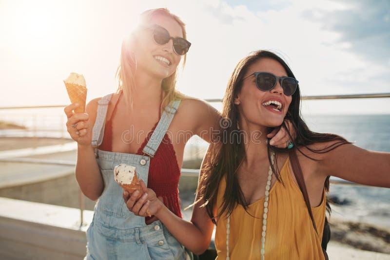 Dwa żeńskiego przyjaciela cieszy się lody wpólnie na lato dniu obrazy stock