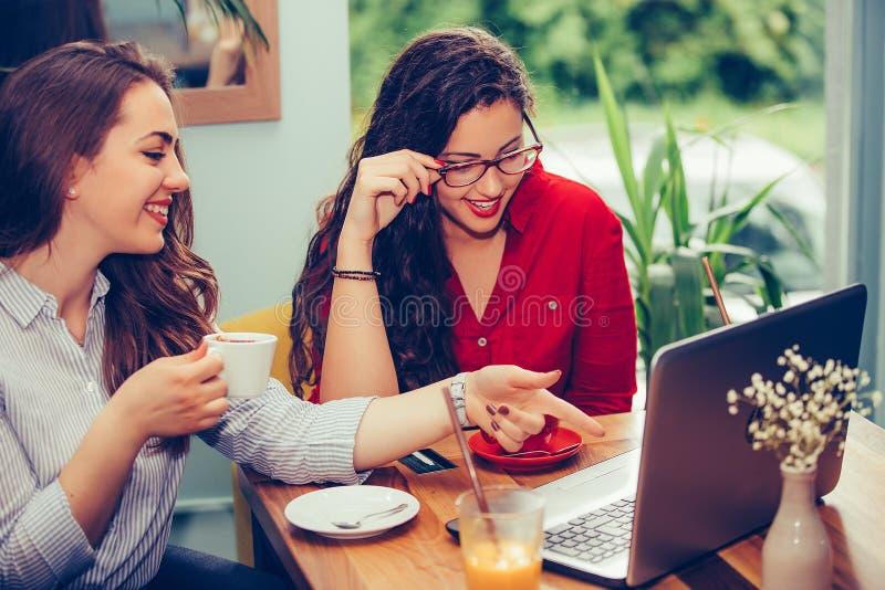 Dwa żeńskiego przyjaciela kupuje na linii z kartą kredytową i laptopu obsiadaniu przy kawiarnią zdjęcia royalty free