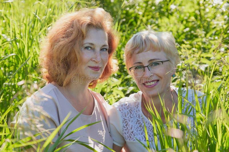 Dwa żeńskiego przyjaciela ma zabawę na naturze Pyzaci i szczupli w średnim wieku kobieta emeryci w zielenieją pole obraz royalty free