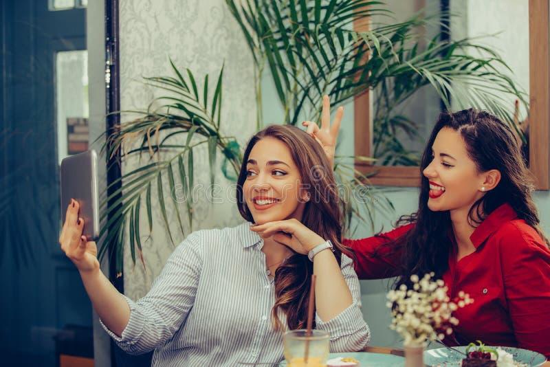 Dwa żeńskiego przyjaciela ma zabawę w kawiarni i bierze selfie z pastylką zdjęcia stock