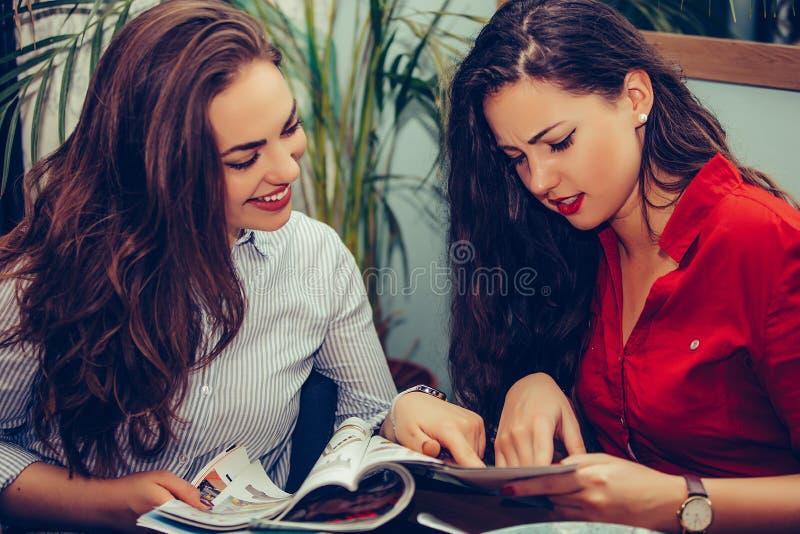 Dwa żeńskiego przyjaciela opowiada magazyn w kawiarni i czyta obraz royalty free