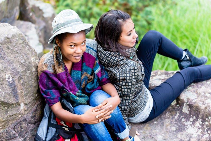 Dwa żeńskiego przyjaciela siedzi na skale obrazy royalty free