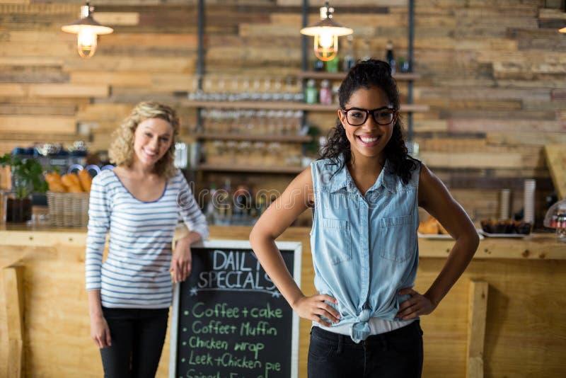Dwa żeńskiego przyjaciela stoi z menu signboard blisko kontuarem obraz royalty free