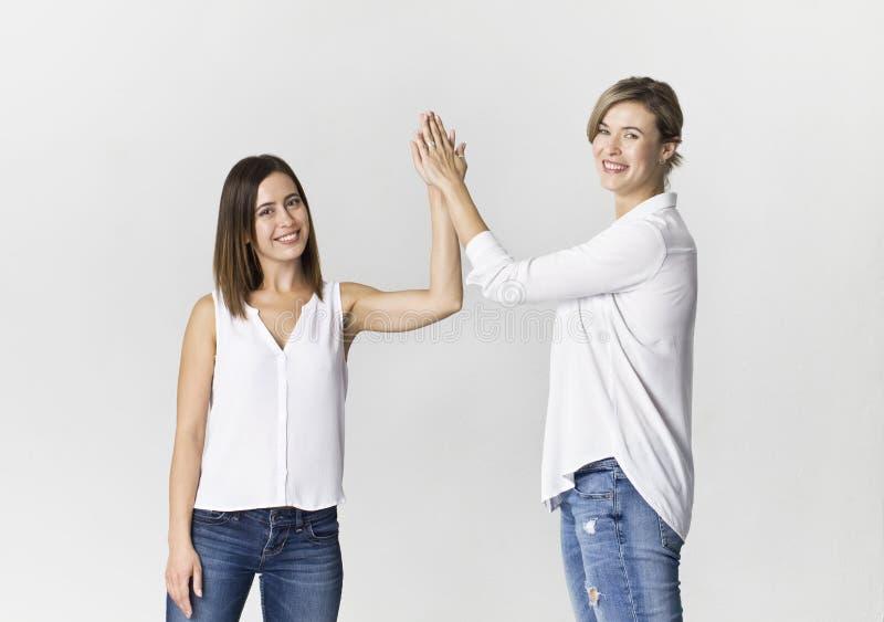 Dwa żeńskiego przyjaciela witają zabawę i mają przy pracownianym backgro zdjęcie royalty free