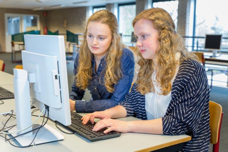 Dwa żeńskiego ucznia pracuje wpólnie na komputerze w sala lekcyjnej fotografia royalty free