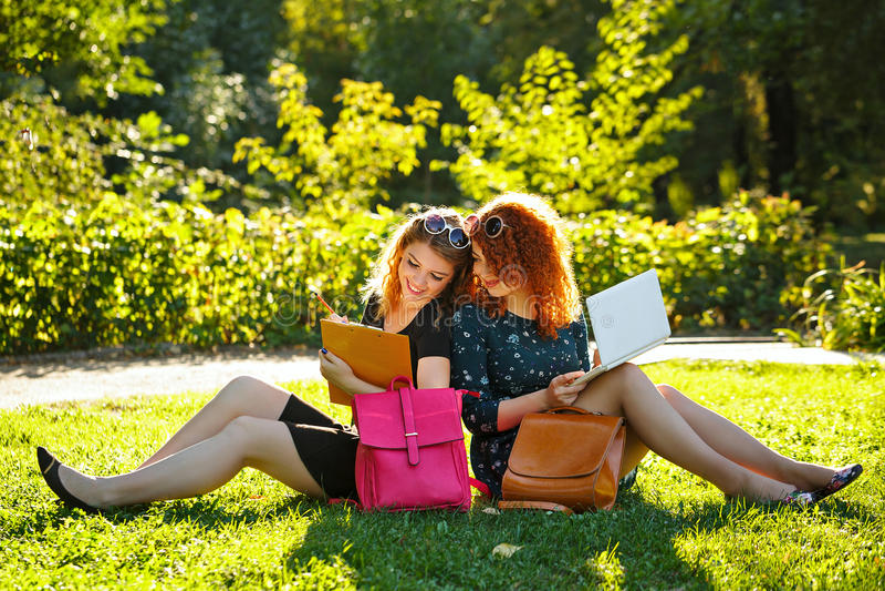Dwa żeńskiego ucznia siedzą na gazonie i patrzeją w laptopie fotografia stock