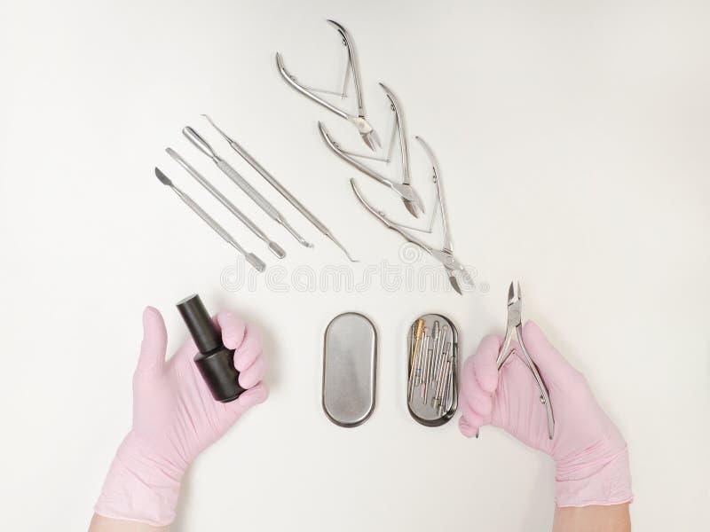 Dwa żeńskiej ręki w rękawiczkach Gwoździ tongs w rękach i połysk Narzędzia dla manicure'u Biały tło, odgórny widok obraz stock