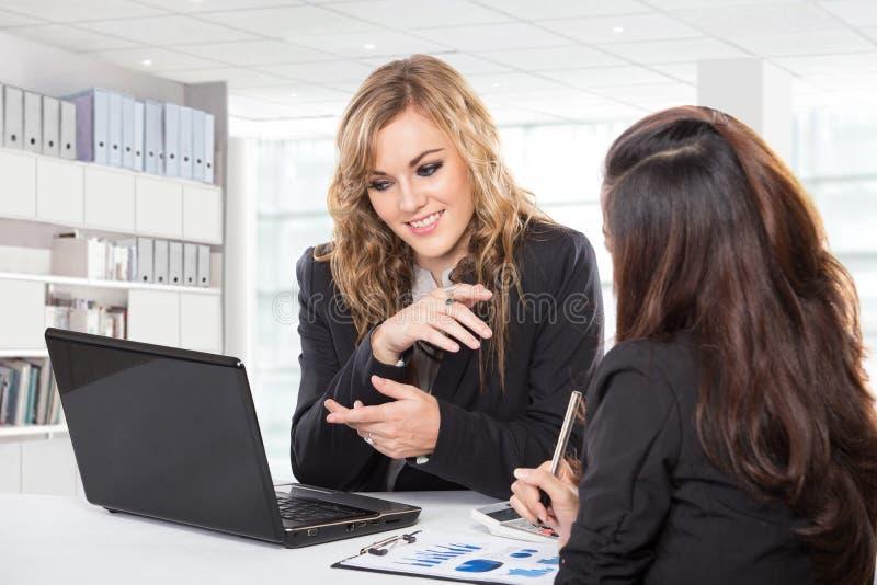 Dwa życzliwego bizneswomanu siedzi nowego pomysłu usin i dyskutuje zdjęcie stock