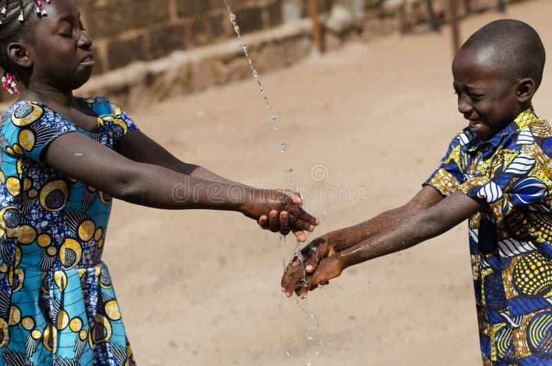Dwa Afrykańskiego dziecka Czyści ręki Outdoors z świeżą wodą zdjęcie royalty free