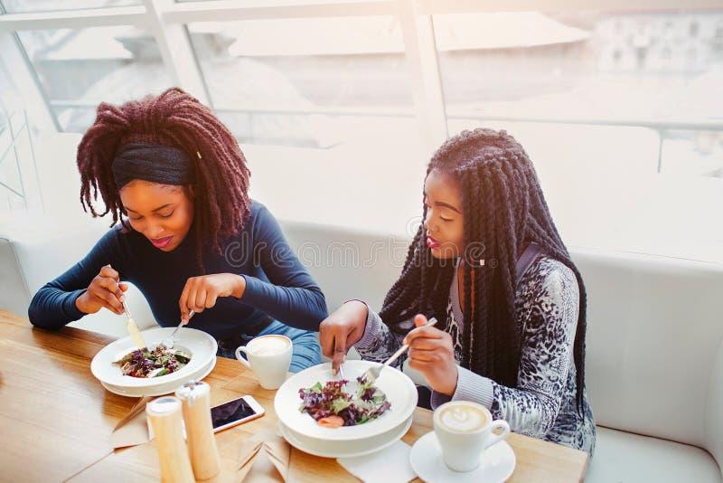 Dwa afrykańskiej kobiety siedzą przy stołem i jedzą jedzenie Koncentrowali Modele są w kawiarni Thy pożera posiłek obrazy stock