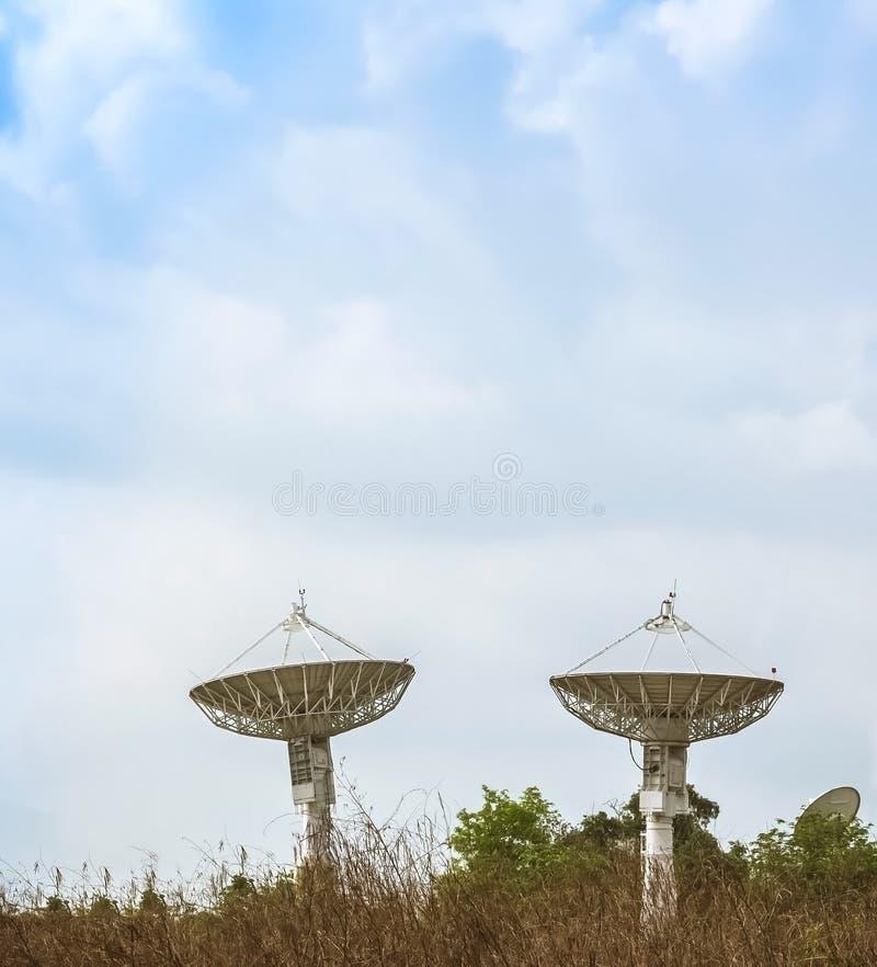 Dwa ampuły antena satelitarna z pięknymi chmurami obraz royalty free