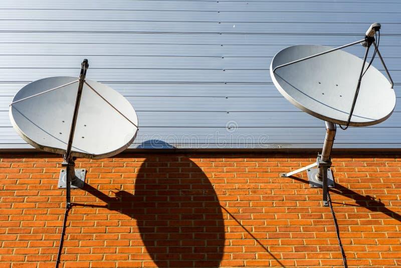 Dwa anteny satelitarnej na ścianie z cegieł zdjęcia stock