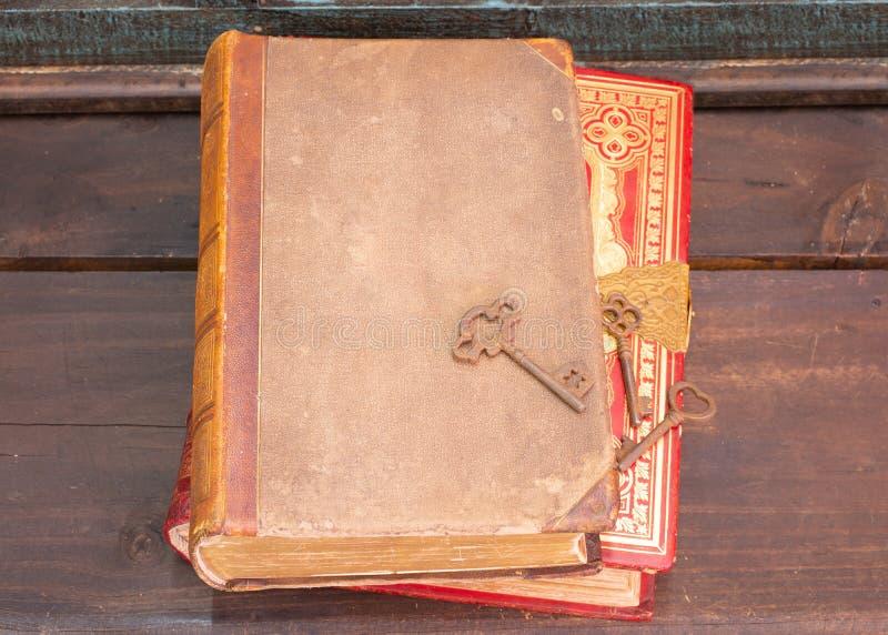 Dwa antykwarskiej książki na drewnianej półce z niektóre starymi zredukowanymi kluczami zdjęcie stock
