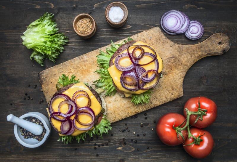 Dwa apetyczny soczysty domowy hamburger z wołowiną, sałatką, kiszonymi ogórkami, serem i cebulami, pomidory, babeczka sezam na ro zdjęcia stock