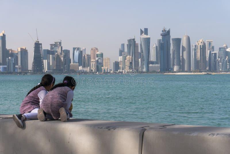 Dwa Arabskiej Środkowej Wielkanocnej małe dziecko dziewczyny Siedzi na Corniche Broadway i Patrzeje na Doha linii horyzontu widok obraz royalty free