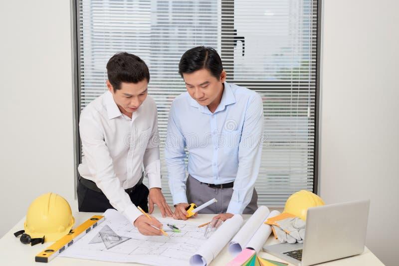 Dwa architekta stoi przy biurkiem i dyskutuje projekt zdjęcie stock