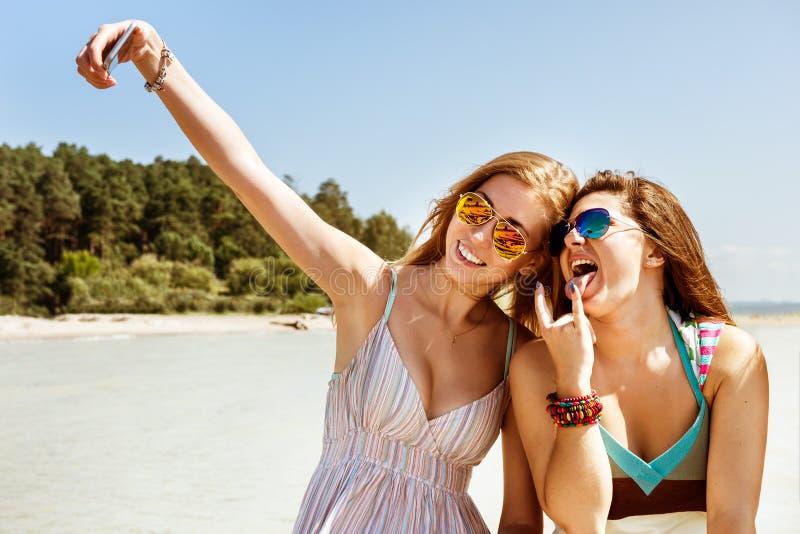Dwa atrakcyjna dziewczyna stoi wpólnie, pozuje selfie plażę i robi, obraz stock