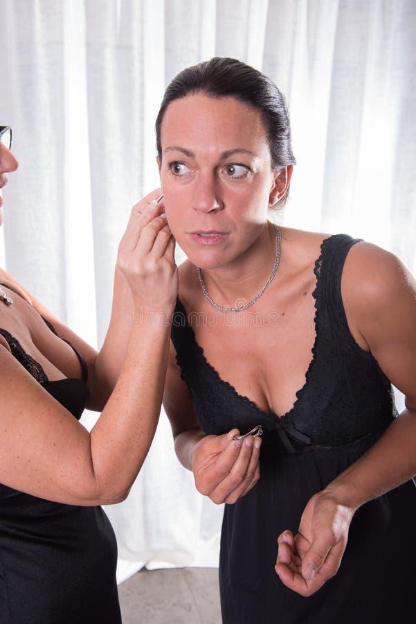 Dwa atrakcyjnej kobiety - jeden stawia inny dalej jej kolczyk obrazy stock