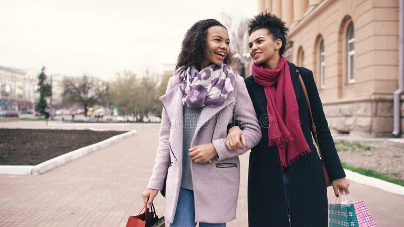 Dwa atrakcyjnej mieszanej biegowej kobiety opowiada w dół ulicę i chodzi z torba na zakupy Dziewczyny zabawę póżniej zdjęcia royalty free