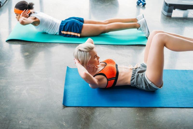 dwa atrakcyjnej wielokulturowej sportsmenki ćwiczy na sprawności fizycznych matach obrazy stock