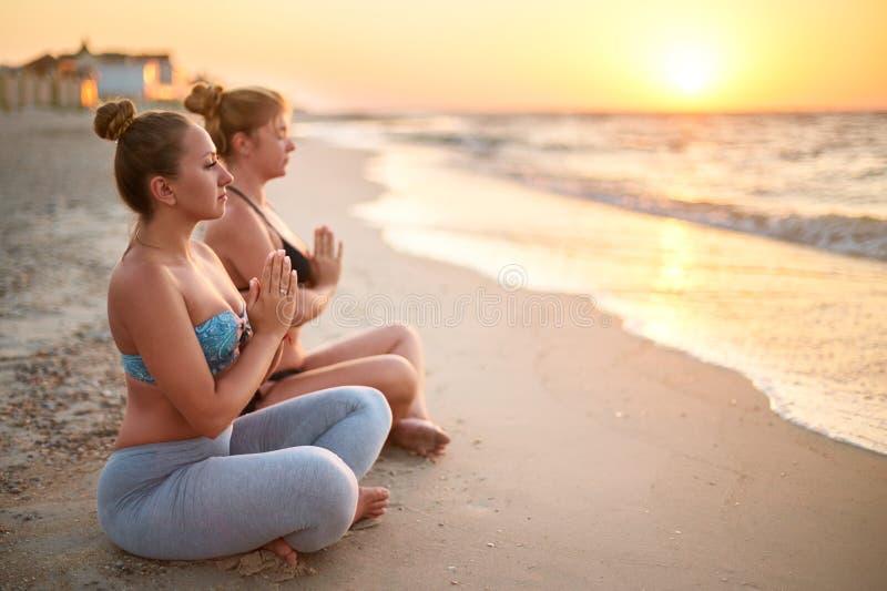 Dwa autentycznej kobiety robi grupowej joga medytacji na plaży przy wschód słońca Dziewczyny relaksuje w lotosowym pozy asana na  fotografia royalty free