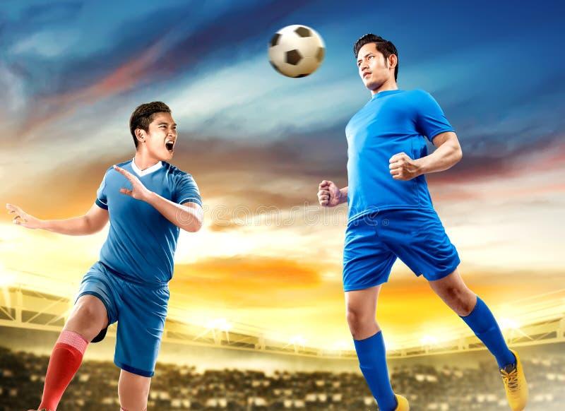 Dwa azjatów gracz futbolu mężczyzny skok w powietrzu przewodzi piłkę pojedynku i obrazy stock