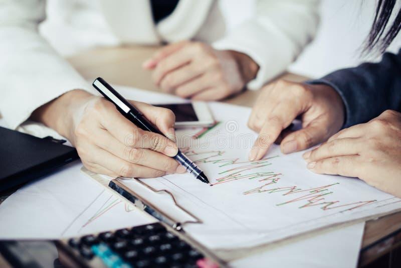 Dwa Azjatycka biznesowa kobieta opowiada wpólnie i pracuje przy biurem analizuje na pieniężnym wykresie zdjęcie royalty free