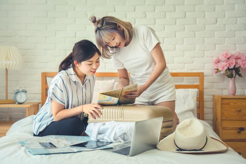 Dwa Azjatyckiego żeńskiego przyjaciela używa mapę dla trasy planowania wakacje wycieczka w pokoju hotelowym obrazy royalty free