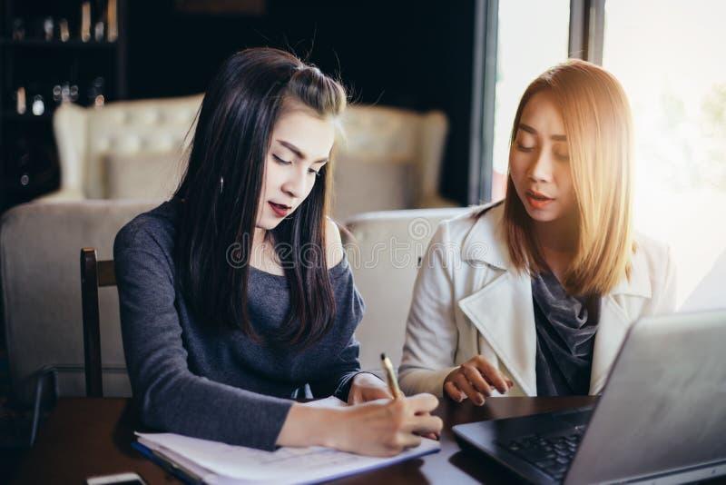 Dwa Azjatyckiej biznesowej kobiety używa notatnika działanie o i dyskusję fotografia stock