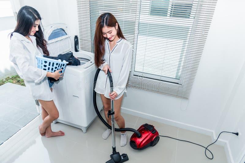Dwa Azjatyckiej kobiety robi sprzątaniu i obowiązek domowy w kuchni Indoors aktywność i styl życia pojęcie Piękna lesbian temat fotografia royalty free