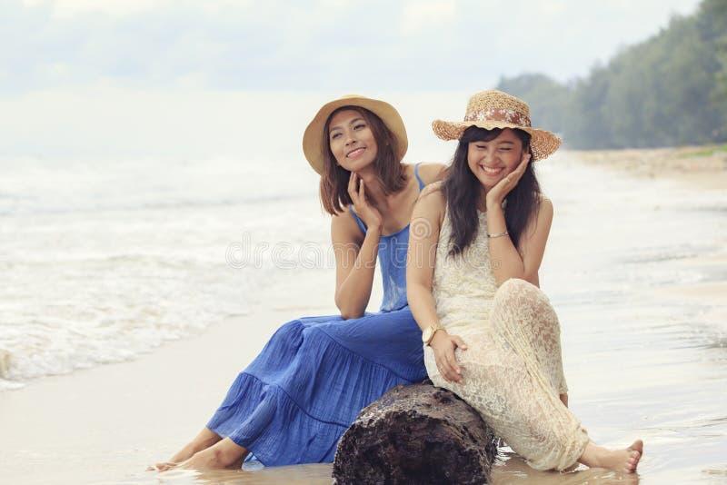 Dwa azjatykcia młoda kobieta relaksuje na morze plaży zdjęcie royalty free