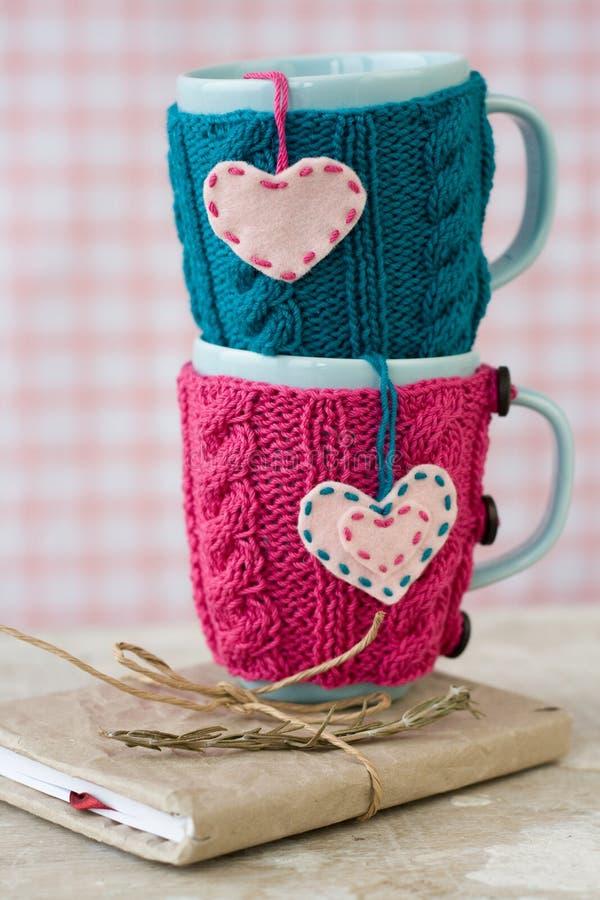 Dwa błękitnej filiżanki w błękita i menchii pulowerze z sercami zdjęcie stock