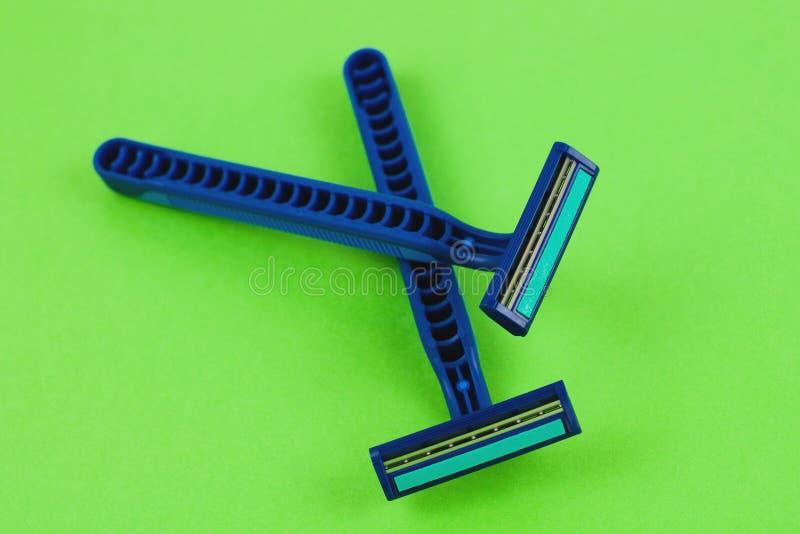 Dwa błękitnej plastikowej rozporządzalnej żyletki z dwa ostrzami i wilgotnym paskiem na pustym zielonym papierze obraz stock