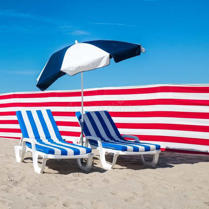 Dwa błękitny przeciw jasnemu niebieskiemu niebu i biali stripy deckchairs fotografia royalty free