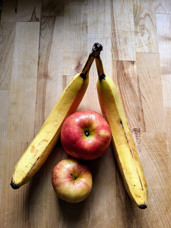 Dwa banana i dwa jabłka na drewnianym stole w naturalnym świetle fotografia royalty free