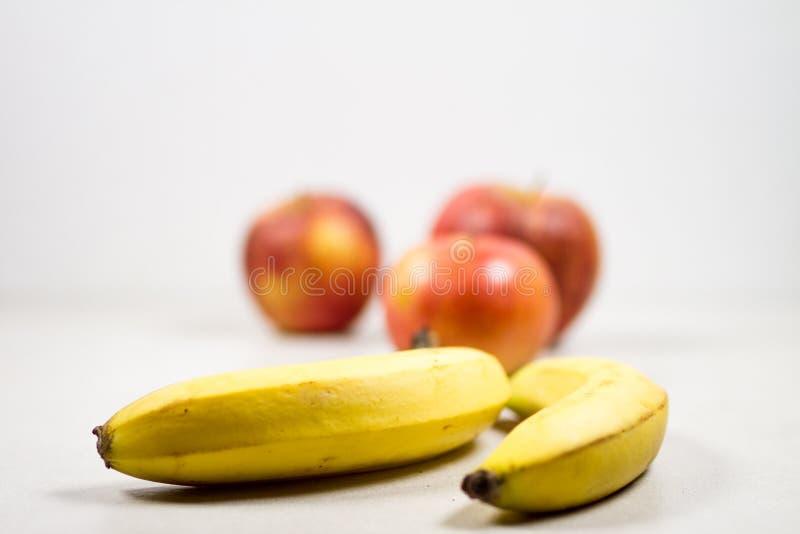 Dwa banana I Trzy jabłek Odosobnionego skład na Białym tle zdjęcia stock