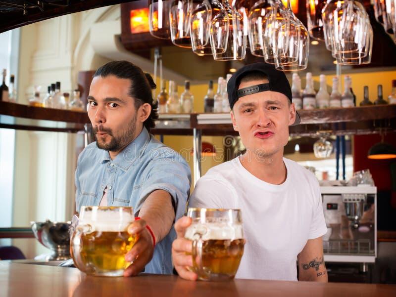 Dwa barmanu robi śmiesznym humorystycznym twarzom i oferuje piwo fotografia royalty free