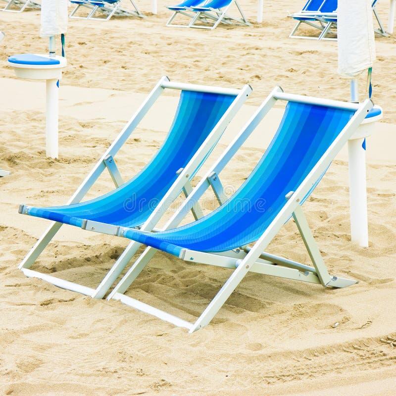 Dwa barwili deckchairs w włoskim nadmorski z piasek diunami w tle fotografia stock